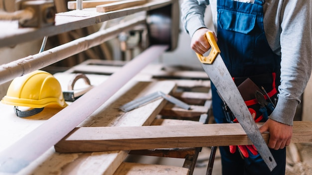 Concetto di carpenteria con uomo che lavora con sega