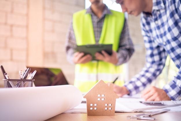 Concetto di casa costruzione casa. ingegneri e team di appaltatori stanno attualmente discutendo il design della struttura della casa.