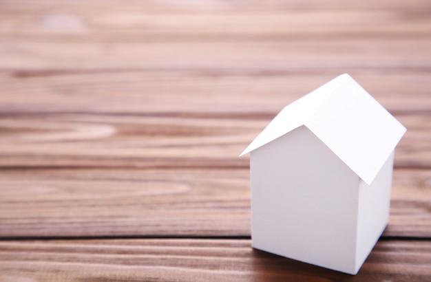 Concetto di casa in carta su fondo di legno marrone.