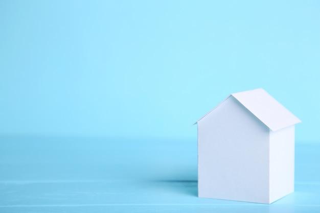 Concetto di casa in carta su sfondo blu.