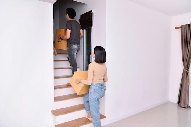 Concetto di casa mobile. le giovani donne asiatiche stanno tenendo le loro cose in una scatola di carta.