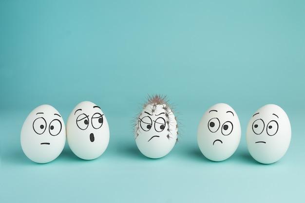 Concetto di cattivo personaggio. uovo spinoso. cinque uova bianche con facce disegnate