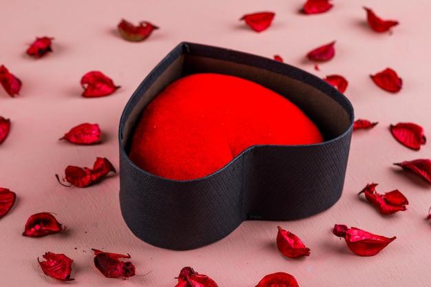 Concetto di celebrazione con cuore rosso in contenitore di regalo, petali di rosa sulla vista di angolo alto della tavola rosa.