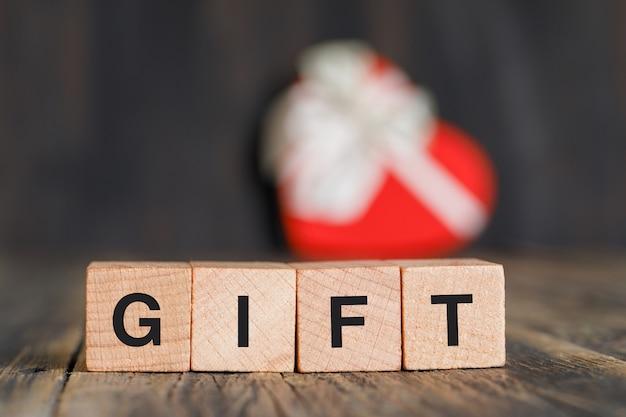 Concetto di celebrazione con il contenitore di regalo, cubi di legno sulla vista laterale della tavola di legno.