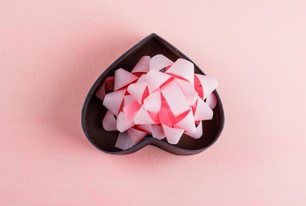Concetto di celebrazione con il nastro dell'arco in contenitore di regalo sulla disposizione rosa del piano della tavola.