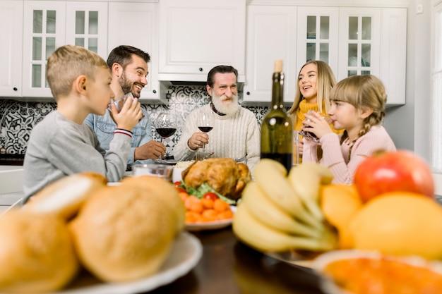 Concetto di celebrazione del ringraziamento. bicchieri di vino e succo tintinnanti sorridenti felici della famiglia sulla cena di festa