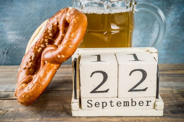 Concetto di celebrazione dell'oktoberfest con boccale di birra in vetro, pretzel e vecchio calendario in legno in stile retrò, sfondo blu e in legno,