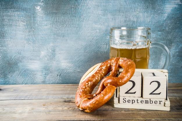 Concetto di celebrazione dell'oktoberfest con tazza di vetro di birra, pretzel e vecchio calendario in legno in stile retrò