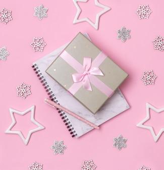 Concetto di celebrazione di inverno natale. blocco note di marmo con la penna e regalo su fondo rosa