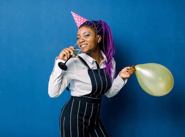 Concetto di celebrazione, festa di compleanno - close up ritratto felice giovane bella donna africana in pantaloni neri e gonna bianca sorridente con palloncino colorato giallo partito. blue pastel studio space.