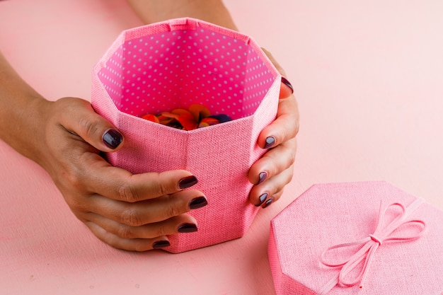 Concetto di celebrazione sulla vista dell'angolo alto della tavola rosa. contenitore di regalo della holding della donna.