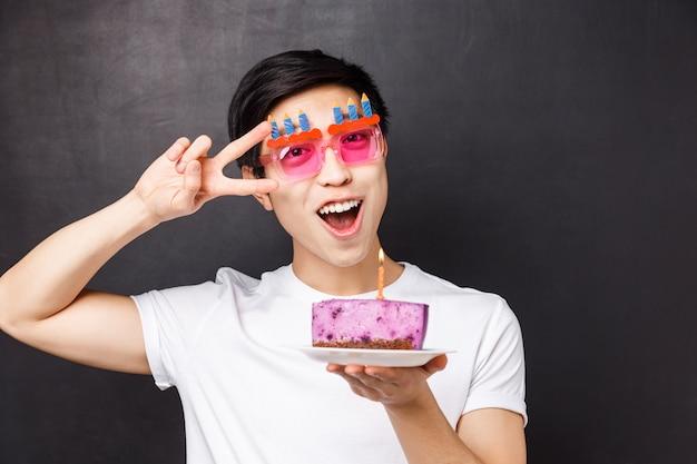 Concetto di celebrazione, vacanze e compleanno. ritratto di close-up di allegro uomo asiatico ottimista in divertenti bicchieri da festa, tenere la torta b-day con candela accesa, fare il segno di pace, esprimere desiderio,