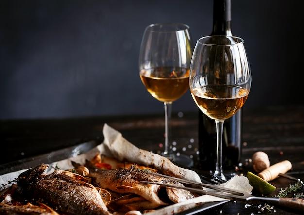Concetto di cena con due bicchieri di vino bianco, pesce al forno