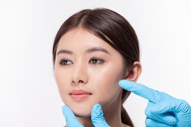Concetto di chirurgia. bella donna asiatica che fa chirurgia facciale.