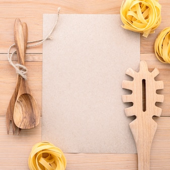 Concetto di cibi italiani e menu carta bianca e mestolo di pasta su legno.
