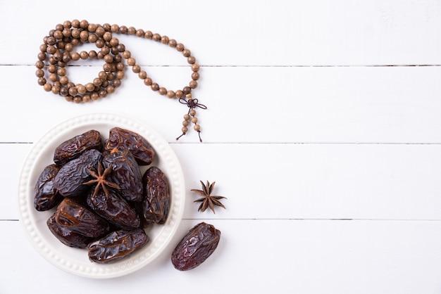 Concetto di cibo e bevande del ramadan. il rosario e le date di legno fruttificano su una tavola di legno bianca