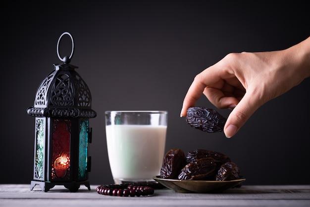 Concetto di cibo e bevande del ramadan. la mano della donna raggiunge fuori ad un piatto con le date