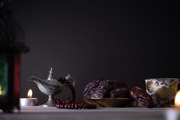 Concetto di cibo e bevande del ramadan. lanterna ramadan con lampada araba, rosario in legno