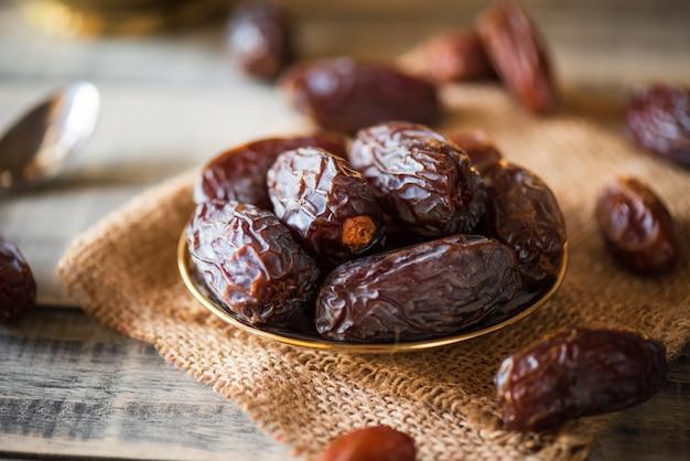 Concetto di cibo e bevande del ramadan. le date fruttificano in una ciotola sulla tavola di legno
