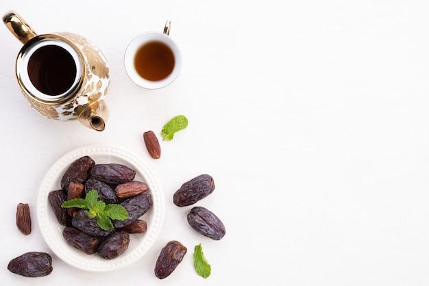 Concetto di cibo e bevande del ramadan. ramadan lantern con tè, data frutta