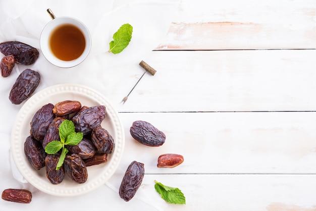 Concetto di cibo e bevande del ramadan. tè con date di frutta e foglie di menta