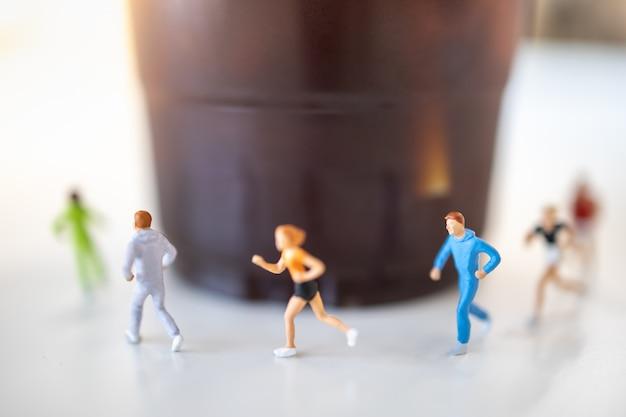 Concetto di cibo e sport chiuda in su del gruppo di figura miniatura del corridore che va in giro tazza di plastica