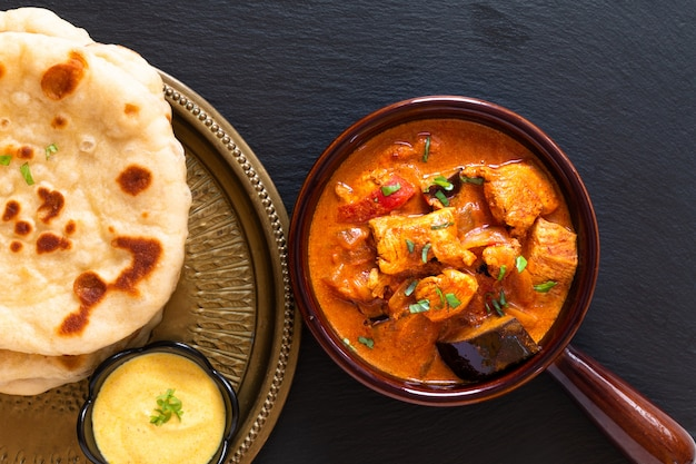 Concetto di cibo in casa tandoori pollo masala al curry con pane naan e salsa di yogurt immersione