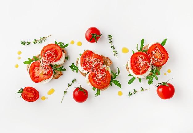 Concetto di cibo italiano. panini aperti con mozzarella, pomodori e rucola in testa, distesi