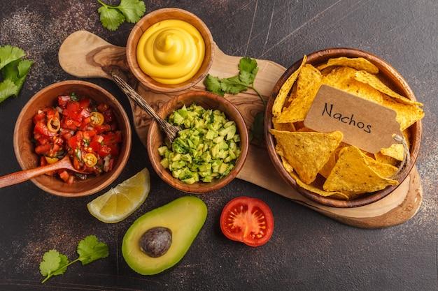 Concetto di cibo messicano. nachos - mais giallo a pezzetti con varie salse in ciotole di legno: guacamole, salsa al formaggio, pico del gallo. vista dall'alto, sfondo di cibo