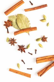 Concetto di cibo mix di baccelli di anice stellato, cannella, alloro e cardamomo spezie biologiche su bianco