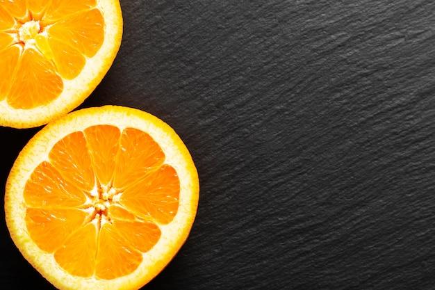 Concetto di cibo organico arancione o pomelo taglio di frutta haft sul bordo di pietra ardesia nera