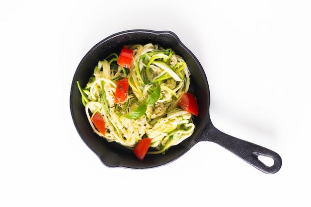 Concetto di cibo sano fatto in casa guilten-free noodles di zucchine, pasta con pomodoro in padella di ferro padella