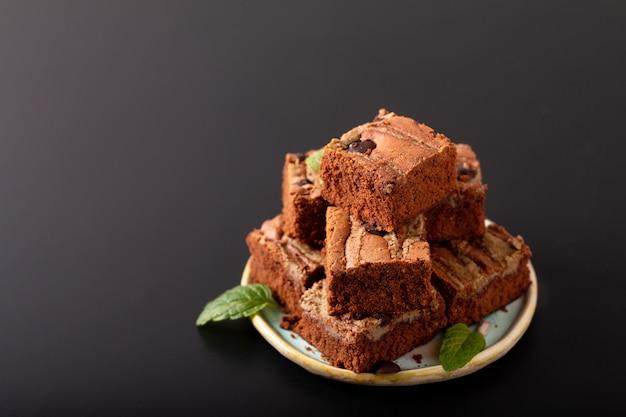 Concetto di cibo sano fudge organici fatti in casa burro semi brownies burro su sfondo nero
