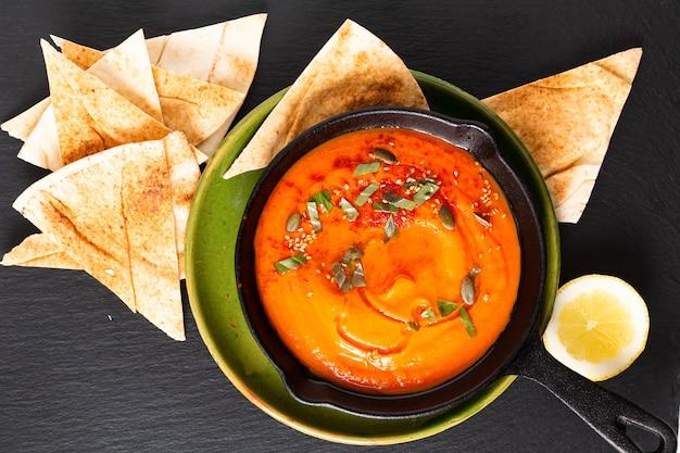 Concetto di cibo sano hummus di zucca in padella di ferro padella con spazio di copia