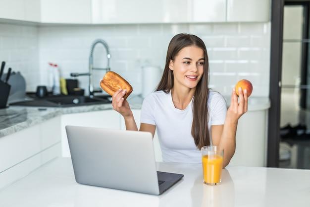 Concetto di cibo sano. scelta difficile. la tua donna sportiva sta scegliendo tra cibi sani e dolci mentre sta in piedi sulla cucina leggera.