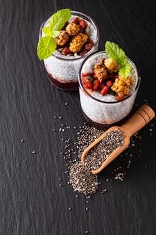 Concetto di cibo sano semi di chia, budino di latte con goji, gelso bianco e mescolare semi secchi in piccolo vetro su sfondo nero lavagna ardesia