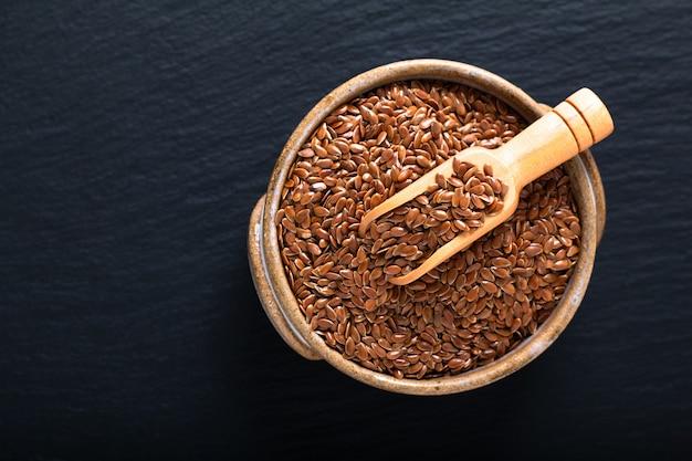 Concetto di cibo sano semi di lino organici in bolw in ceramica sul bordo di ardesia nera con spazio di copia