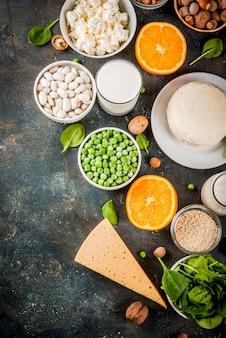 Concetto di cibo sano. set di alimenti ricchi di calcio - latticini e prodotti vegani ca sfondo blu scuro