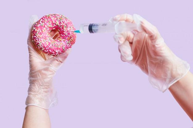 Concetto di cibo spazzatura. mani, siringa e ciambella rosa.