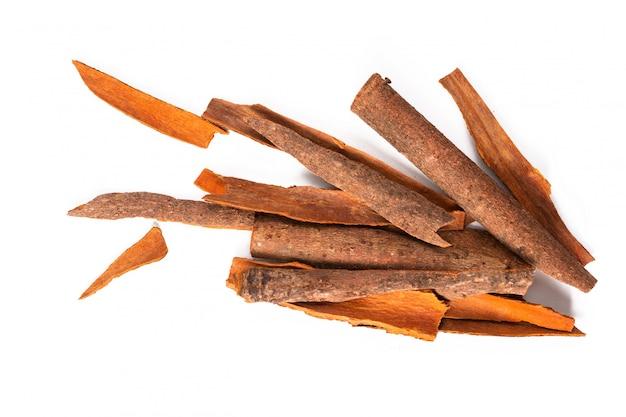 Concetto di cibo spezie orientali cannella cassia bark sticks su bianco