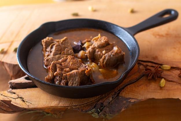 Concetto di cibo stufato di carne piccante in padella in ghisa con spazio di copia