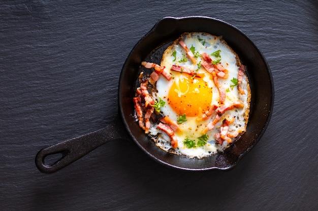 Concetto di cibo uova fritte e pancetta in padella di ghisa con copia spazio