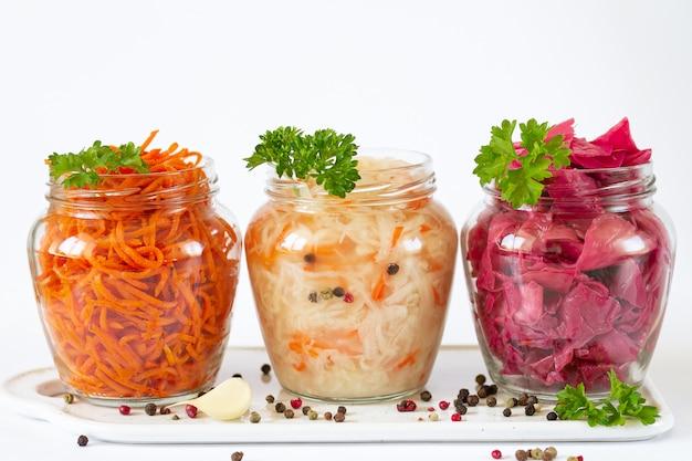 Concetto di cibo vegetariano fermentato e conservato. crauti, cavolo rosso marinato e carota in barattoli di vetro aperti