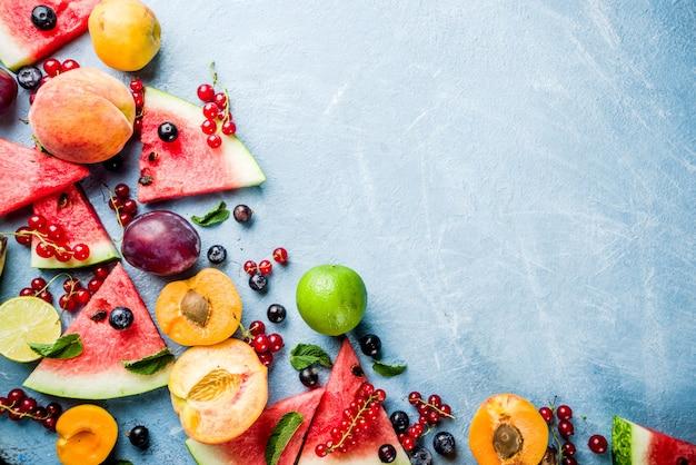 Concetto di cibo vitaminico, vari frutti e bacche anguria pesca menta prugne albicocche ribes mirtillo