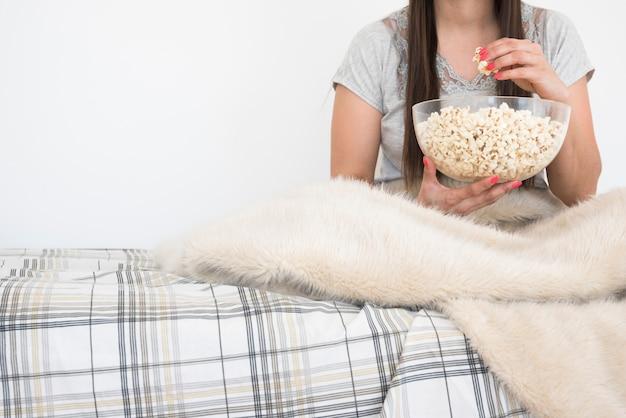 Concetto di cinema con donna che mangia popcorn