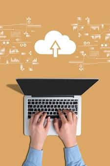 Concetto di cloud storage. mani su un laptop con uno sfondo arancione.