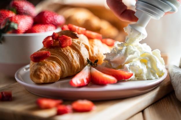 Concetto di colazione con tazza di caffè, cornetti, panna e frutti di bosco freschi.