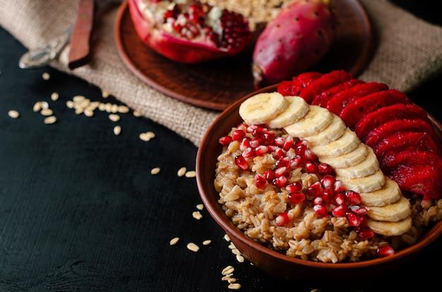 Concetto di colazione dieta sana. porridge di avena con banana, semi di melograno e frutti di cactus opuntia. copia spazio.