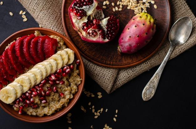 Concetto di colazione dieta sana. porridge di avena con banana, semi di melograno e frutti di cactus opuntia