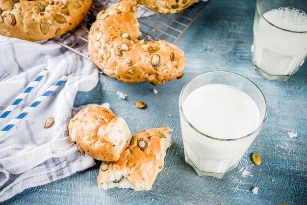 Concetto di colazione sana, bagel di cereali fatti in casa con un bicchiere di latte